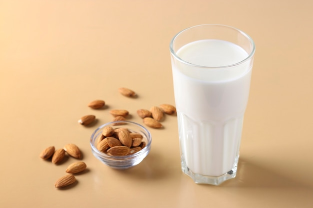 Glass with fresh almond milk and almonds on beige surface, healthy vegan milk replacer, horizontal format, space for text, closeup