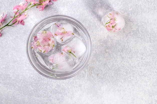 Glass with fresh clean clear water and ice cubes with delicate pink flowers.