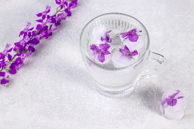 Glass with fresh clear water and ice cubes with purple flowers.