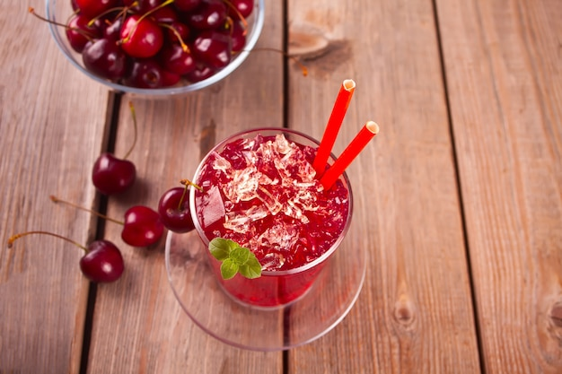 Glass with fresh homemade cherry sweet iced tea or cocktail, lemonade with mint. refreshing cold drink. summer party.