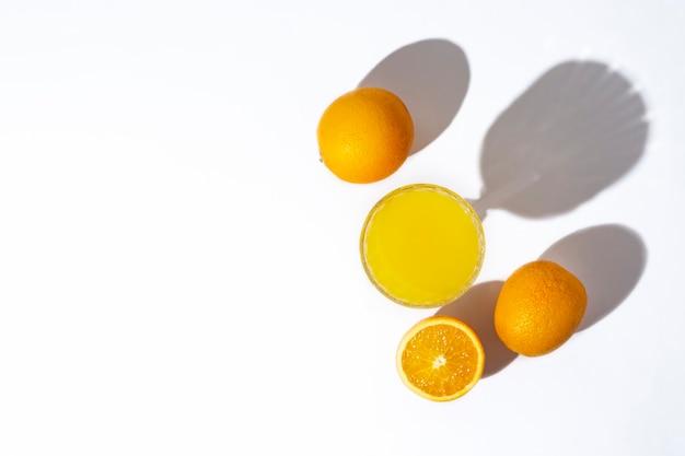 明るい背景にフレッシュ ジュースとオレンジの入ったグラス。平面図、フラット レイアウト