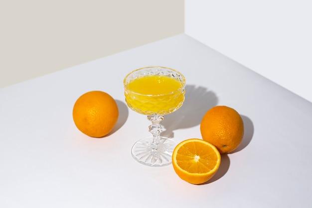 明るい背景にテーブルにフレッシュ ジュースとオレンジを入れたグラス。平面図、フラット レイアウト