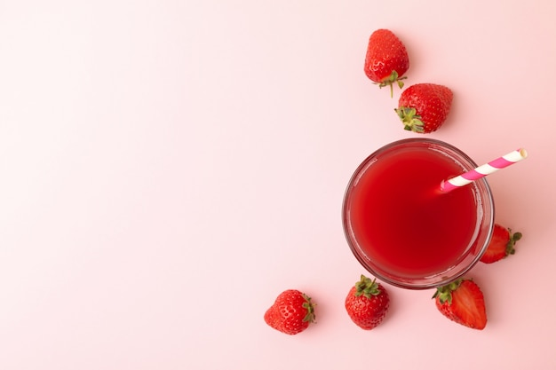 Glass with fresh strawberry juice on pink