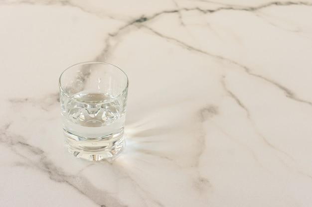 Стекло с пресной водой на мраморном столе. место для текста.