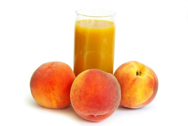 Стекло со свежеприготовленным персиковым соком на белом фоне