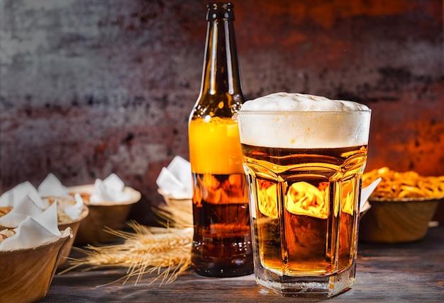 濃い色の木製の机の上に、ボトルとプレートの近くに、注ぎたてのビールと泡の頭が付いたグラス。食品および飲料の概念