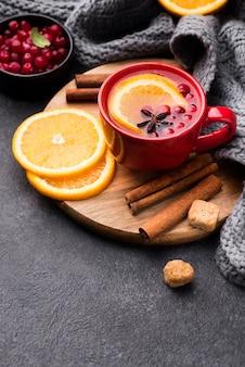 Стакан с фруктовым ароматом чая на деревянной доске
