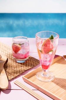 Glass with grapefruit drink in tray