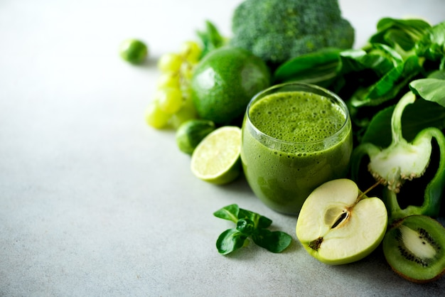 Glass with green health smoothie, kale leaves, lime, apple, kiwi, grapes, banana, avocado, lettuce. raw, vegan, vegetarian, alkaline food concept.