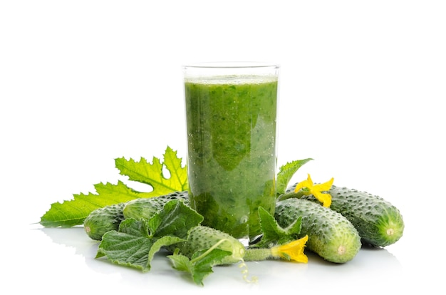 Glass with green smoothie and cucumbers, flowers, leaves isolated