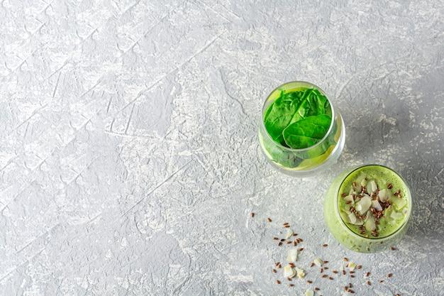 灰色の背景にほうれん草、アボカド、セロリ、キウイ、ココナッツミルクから緑のスムージーとガラス