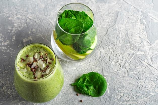 ほうれん草、アボカド、セロリ、キウイ、ココナッツミルクのグリーンスムージーを添えたグラスに、ココナッツフレークと亜麻仁を添えて