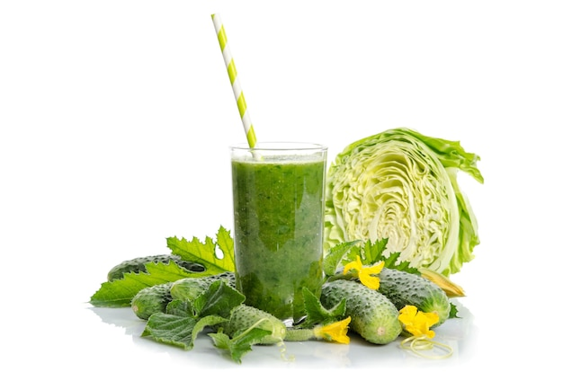 Glass with green smoothie and vegetables, leaves, flowers isolated
