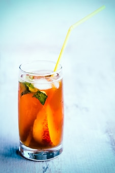 A glass with homemade ice tea, peach flavored.