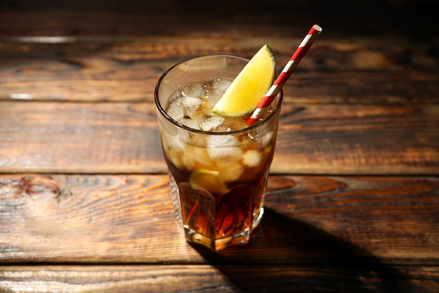 Glass with ice cola and lime slice on wooden background