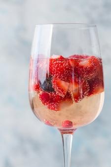 Стекло со льдом лето домашнее холодный красный сангрия коктейль с клубникой в стакан на синей стене. концепция отдыха, лето