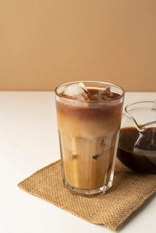 Glass with iced coffee on table