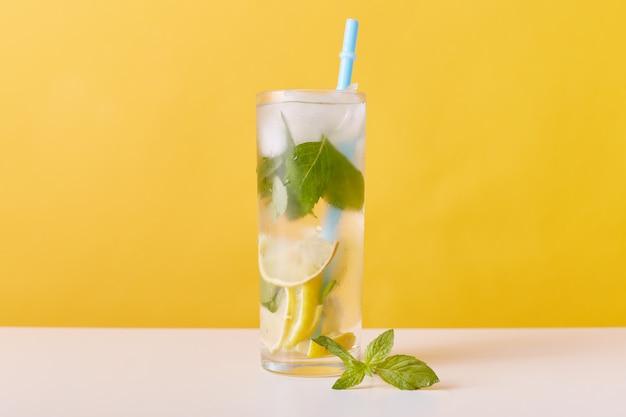 Стакан с чаем со льдом, дольками лимона, мятой и кубиками льда
