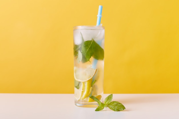 Glass with iced tea with lemon slices, mint and ice cubes