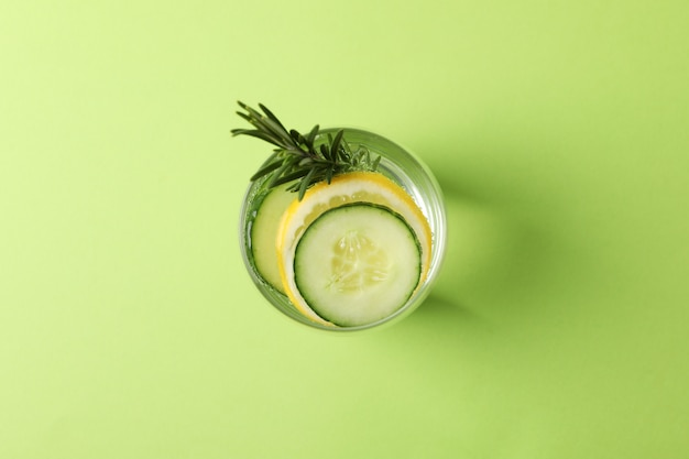 Glass with infused cucumber water on green background, top view