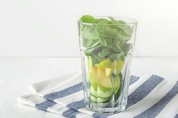 Стакан с ингредиентами для зеленого смузи: шпинат, яблоко, огурец. домашняя еда. веганский здоровый детокс, диетические напитки и напитки для похудания.