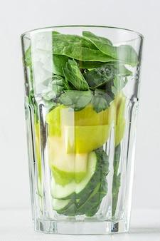 Стакан с ингредиентами для зеленого смузи: шпинат, яблоко, огурец