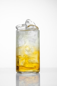 Стекло с соком и льдом на белом фоне.