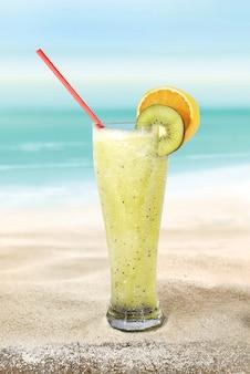 해변 모래에 키위와 오렌지 주스가 든 유리 프리미엄 사진