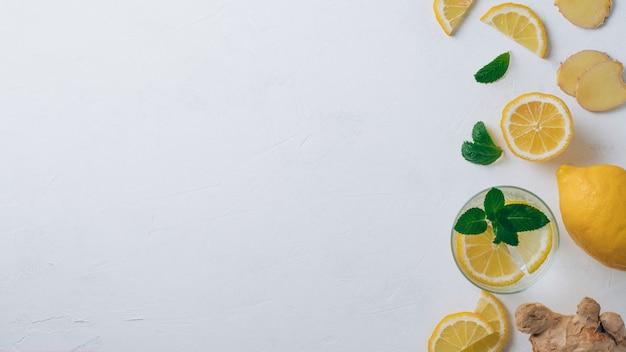 Стакан с лимонадом и ингредиентами для приготовления. имбирь, лимон, мята на белой поверхности. вид сверху, копия пространства. баннер