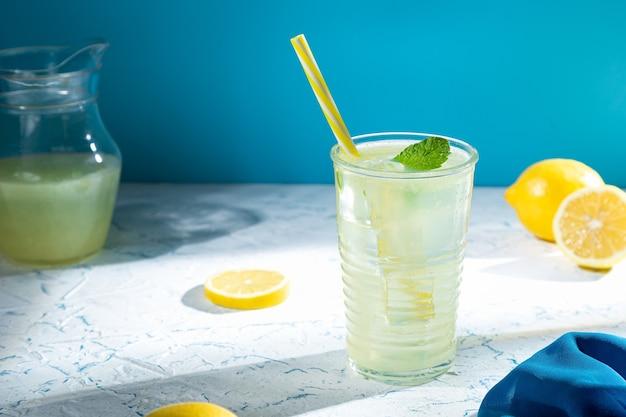 Стекло с лимоном и лимонами на синем светлом фоне.