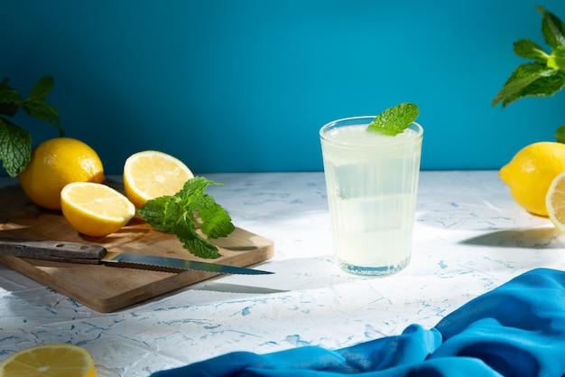 Стакан с лимоном и лимонами на деревянном столе, холодный освежающий напиток со льдом на светлом фоне.