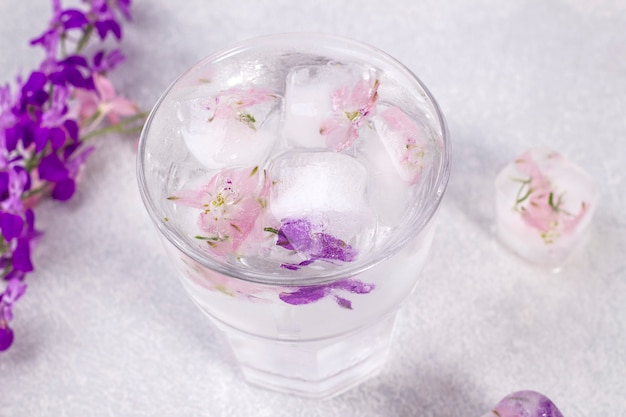 Glass with lemonade and ice cubes with purple and soft pink flowers.