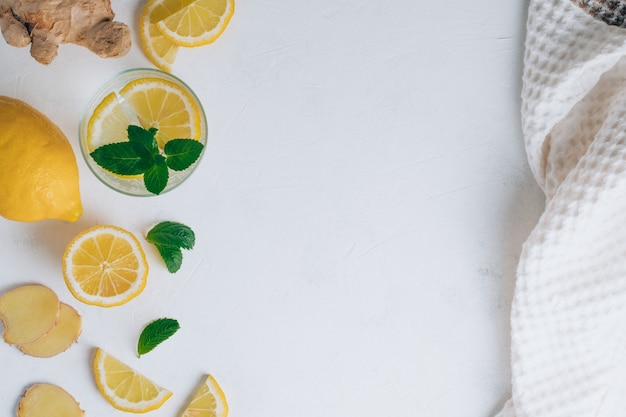Glass with lemonade and ingredients for cooking. ginger, lemon, mint and towel on white surface. flat lay. copy space