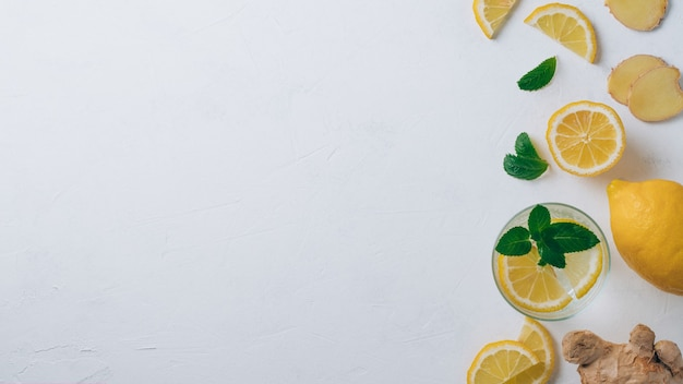 Glass with lemonade and ingredients for cooking. ginger, lemon, mint on white surface. top view, copy space. banner