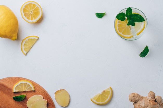Glass with lemonade and ingredients for cooking. ginger, lemon, mint on white surface. wooden tray. top view. copy space