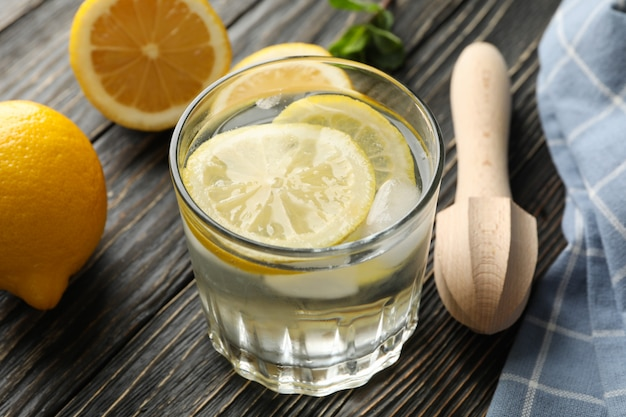 Glass with lemonade and ingredients on wooden surface, close up