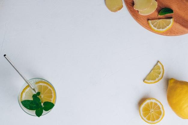 金属ストローと料理の材料とレモネードとガラス。白い表面に生姜、レモン、ミント。木製トレイ。フラットレイ。上面図。コピースペース