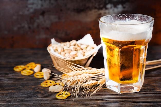 軽いビールとピスタチオ、小麦、散らばった小さなプレッツェルとピーナッツが暗い机の上にあるプレートの近くの泡の頭を持つガラス。食品および飲料の概念