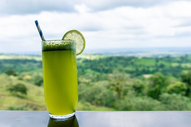 Glass with lime juice decorated with a slice of lime on a table with forest views. costa rica