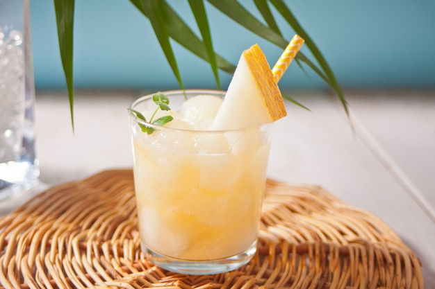 Glass with melon cocktail on a white table with the palm leaf in tropical theme