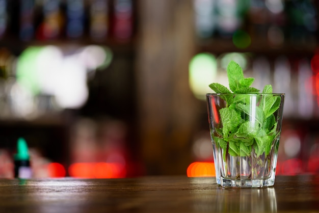 A glass with mint stands on wooden rack in the bar