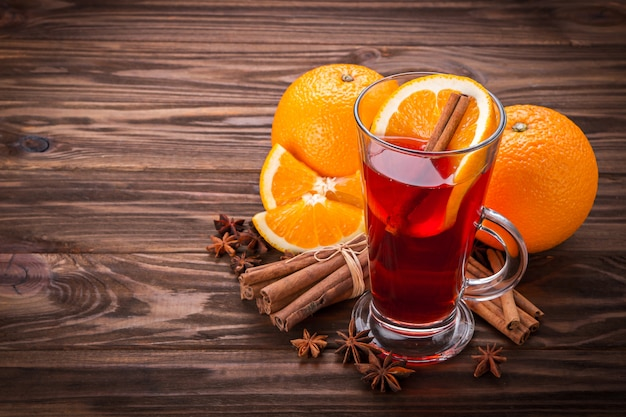 Glass with mulled wine, spices and fruits on wooden background