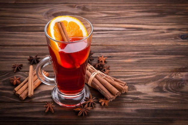 Glass with mulled wine with cinnamon and anise on wooden background