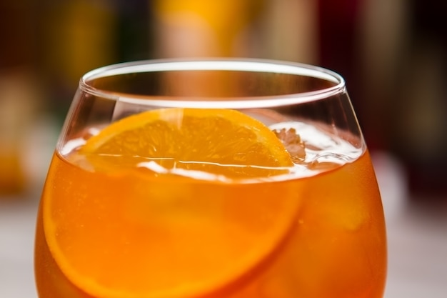 Glass with orange beverage. slice of fresh orange. aperol spritz served at nightclub. alcohol and soda water.