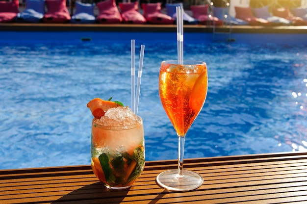 A glass with an orange cocktail near the pool