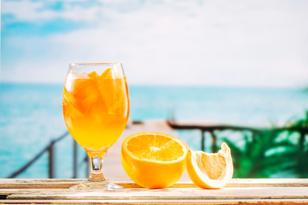 Glass with orange drink and sliced orange on wooden table