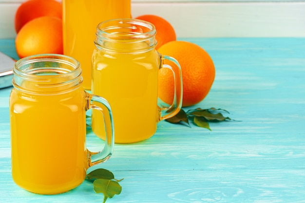 Glass with orange juice on green wooden table