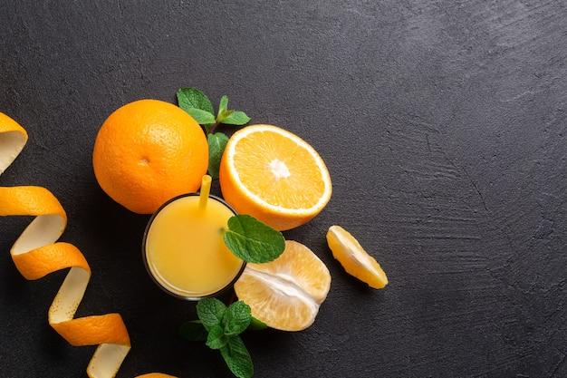 オレンジジュースとグラス。ほぼ全体、半分と1つのオレンジスライス。ミントの小枝がいくつかあります。スペースをコピーします。