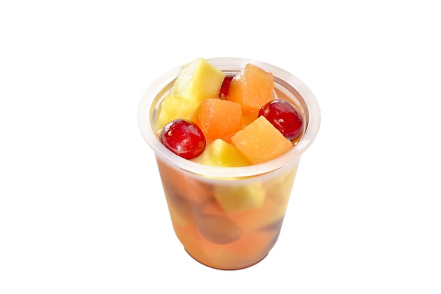 Glass with pieces of fruit and whole grapes in syrup