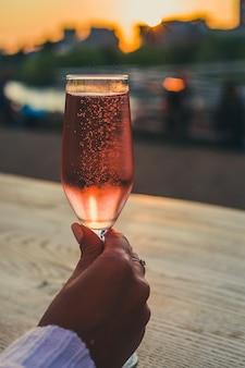 女性の手にピンクのシャンパンとガラス